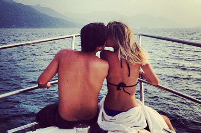 Couple enjoying on front deck of private yacht in Dubai cruising across the blue sea