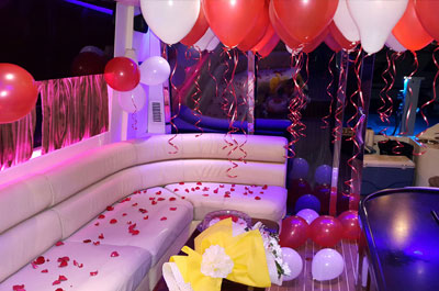 Party Yacht in Dubai beautifully decorated for birthday with red and white balloons, rose petals and cake in lounge