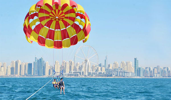 Family experiencing adventurous parasailing through the sky while towing behind a yacht near Jumeirah Beach in Dubai