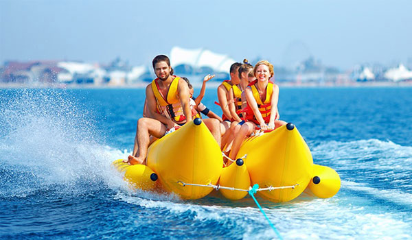 Thrillseekers having adrenaline-pumping experience on banana boat ride in the middle of the water in Dubai